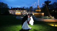Wedding couple kissing outside at night in front of Fountain